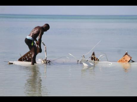 This man was among several persons who brave the crocodile-infested waters yesterday to get close to the wreckage of the twin engine Cessna that crashed at White Sands Beach, Rocky Point, Clarendon on Saturday.