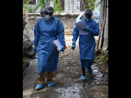 Community health aides walk through sections of Church Corner in Morant Bay , St Thomas, last August after the community was placed under quarantine to prevent the spread of COVID-19.