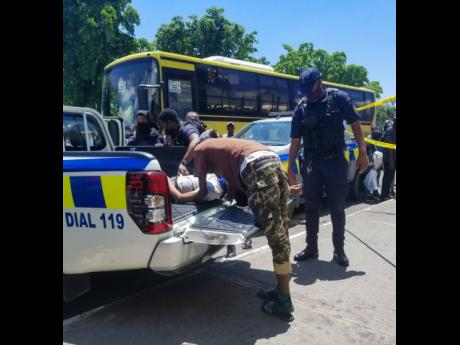 A gunshot victim is placed in a police service vehicle following an attack on Orange Street, downtown Kingston, earlier this month.