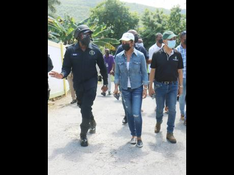 Senior Superintendent of Police Vernon Ellis (left), Member of Parliament of St James West Central Marlene Malahoo Forte  (centre) and Dr Horace Chang, the minister of national security, tour a section of Granville, St James following Sunday morning's bloody attack.
