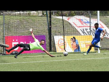 Molynes United's Ackeem Stewart (right) clears the ball off the line after goalkeeper Leon Taylor was beaten during their preliminary round Jamaica  Premier League football match against Tivoli Gardens on September 11. The game ended 1-1.