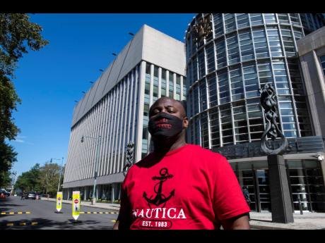 An unidentified supporter of R&B singer R. Kelly, wears a mask reading 'Free R. Kelly' outside Brooklyn Federal Court House on Monday.