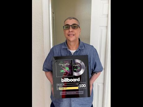 Johnny Wonder with the Billboard Hot 100 plaque.